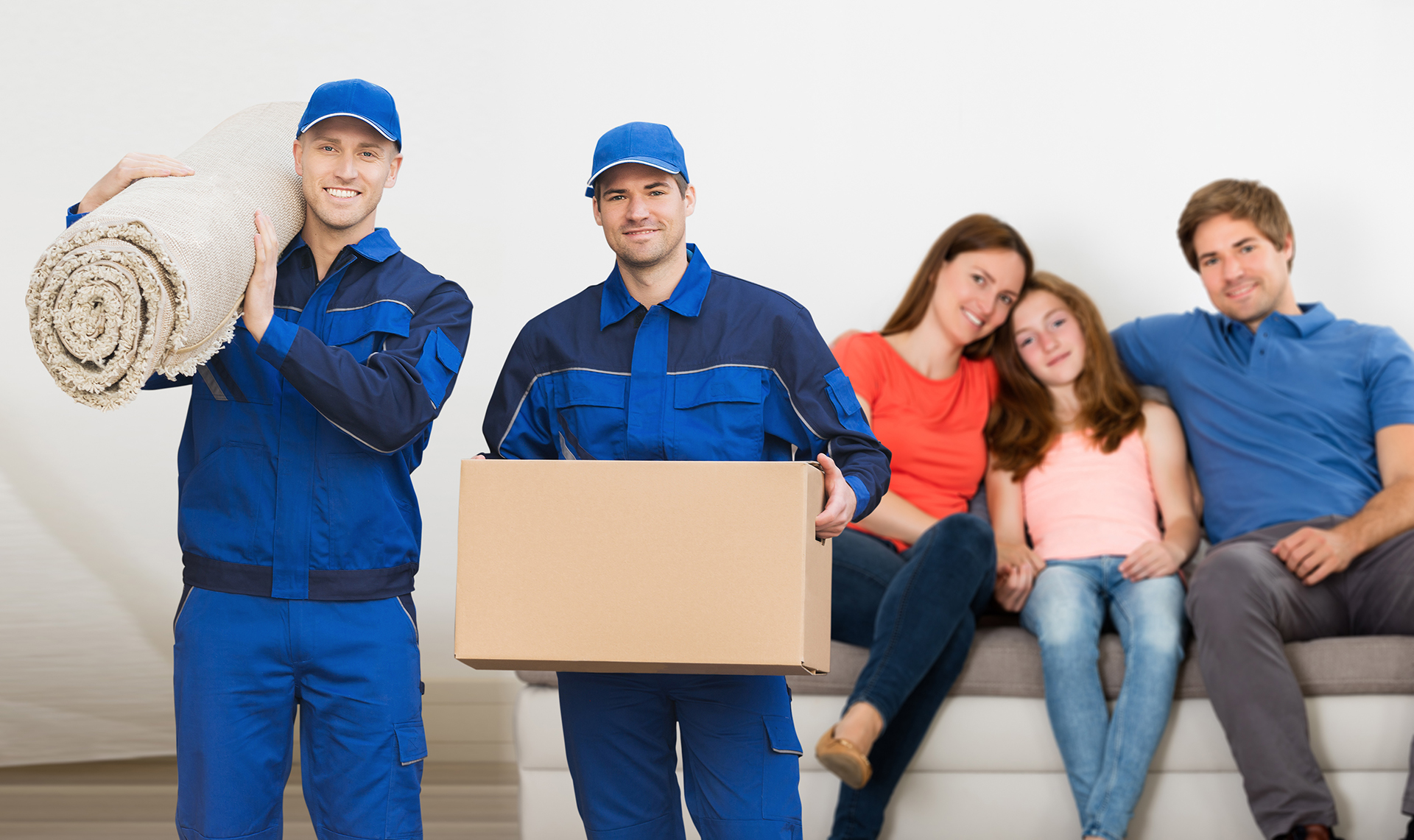 Two Smiling Mover  Men Carrying Cardboard Box And Carpet In Front Of Family